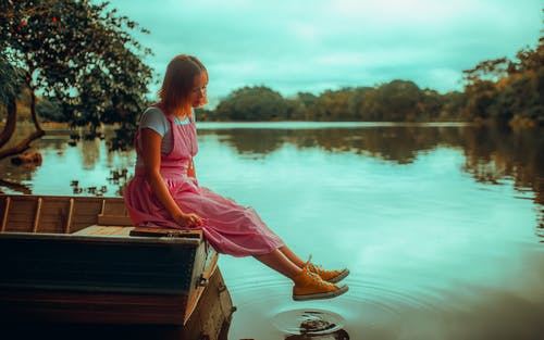 Girl in Pink Dress Sitting on Brown Wooden Dock