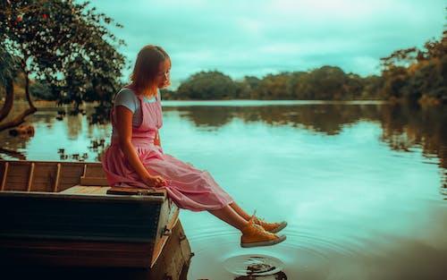 Ragazza In Vestito Rosa Che Si Siede Sul Bacino Di Legno Marrone