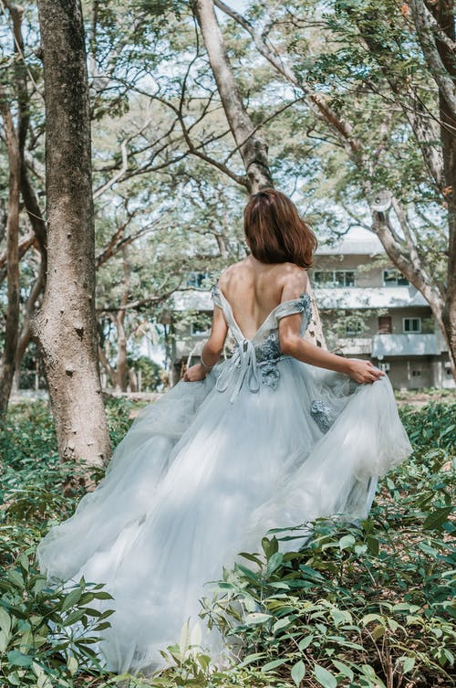 Back view of unrecognizable young female in elegant white gown walking among green trees in garden during daytime