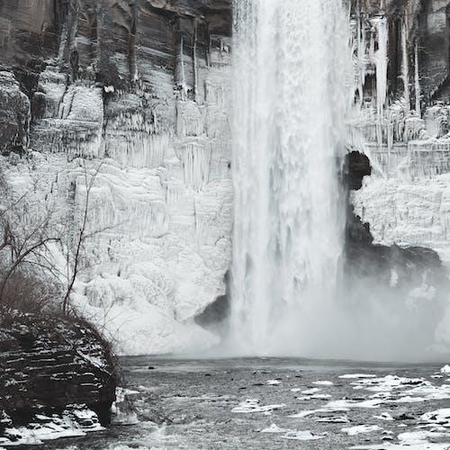 Orang Dengan Jaket Hitam Berdiri Di Tanah Tertutup Salju Dekat Air Terjun