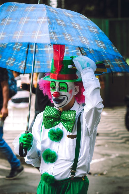 Anonymous male clown in funny costume and pink wig walking on street with umbrella and looking at camera