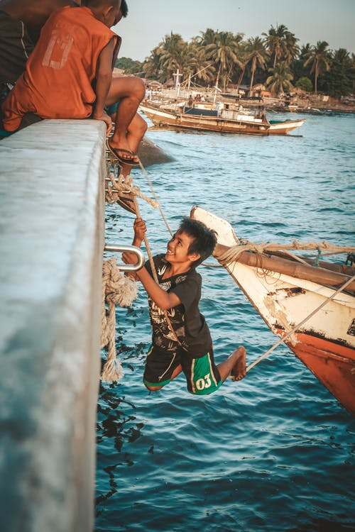 Boys playing on aged boat in tropical sea