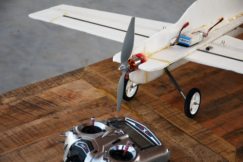 White Remote Control Airplane on Wooden Table