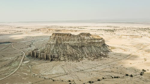 Drone view of majestic stone formation in middle of arid sandy canyon with blue sky