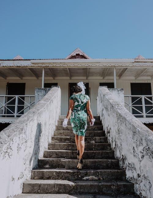 Wanita Dengan Gaun Bermotif Bunga Hijau Dan Putih Berjalan Di Tangga Beton Abu Abu