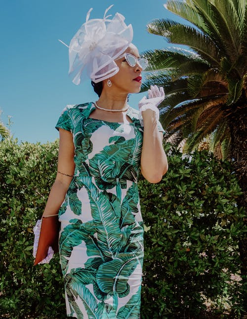 Woman in Green and White Floral Dress With White Flower on Her Head
