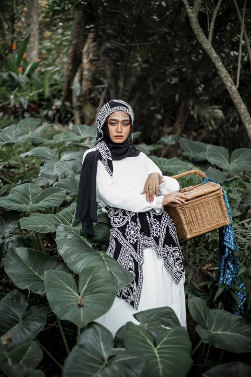 Woman in Black and White Floral Hijab Holding Brown Woven Basket