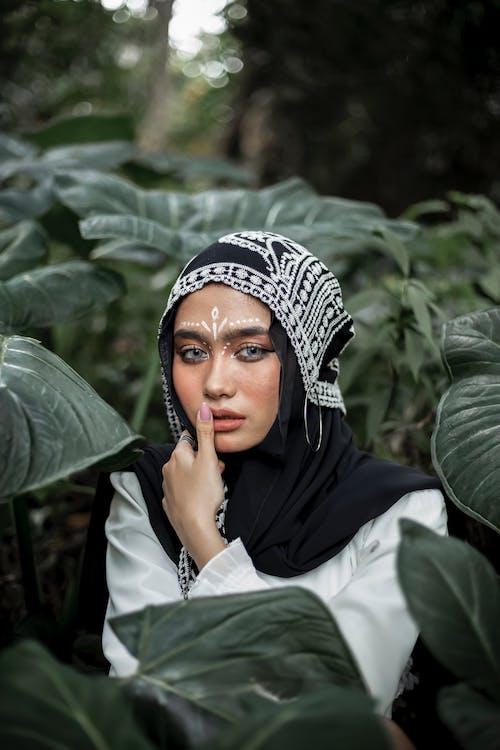 Mujer En Hijab Negro Cerca De Hojas Verdes