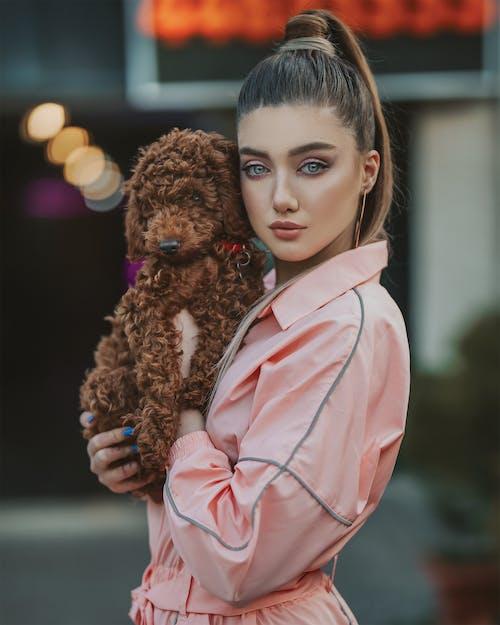 拿着棕色狗的粉红色外套的女孩