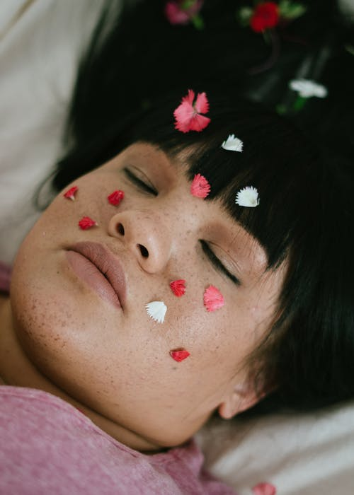 Sensual plump ethnic lady relaxing on bed with flower petals on face and with closed eyes