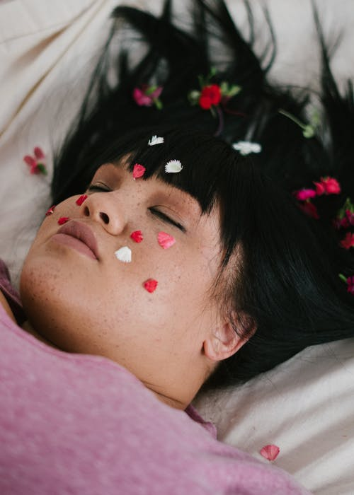 Sensual plump ethnic lady lying on bed with flower petals on face and with closed eyes