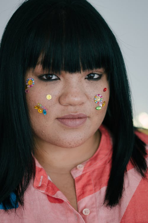 Young ethnic lady with glitter paint on cheeks and face