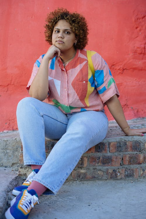 Thoughtful young plus size ethnic lady sitting on stone stair near pink wall in street