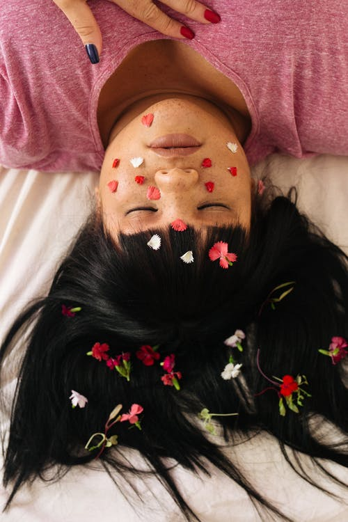 Sensual young ethnic overweight lady lying on bed with petals on face