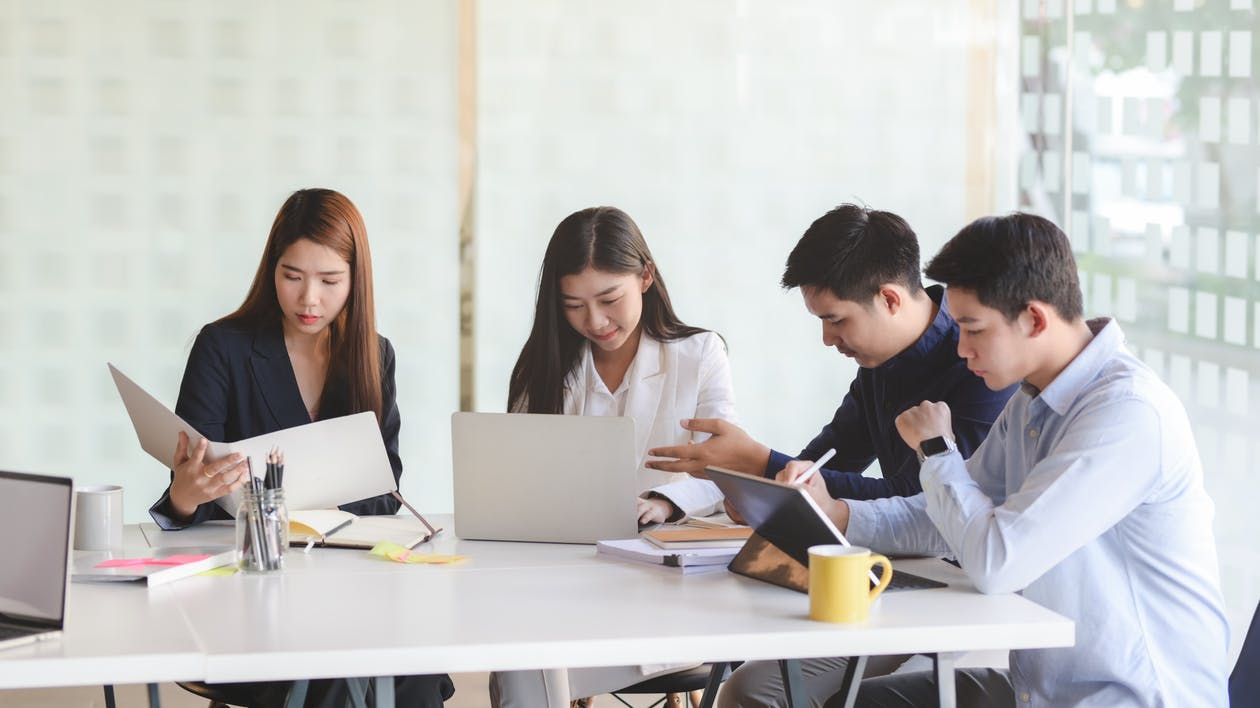 Ethnic colleagues working on project in modern office