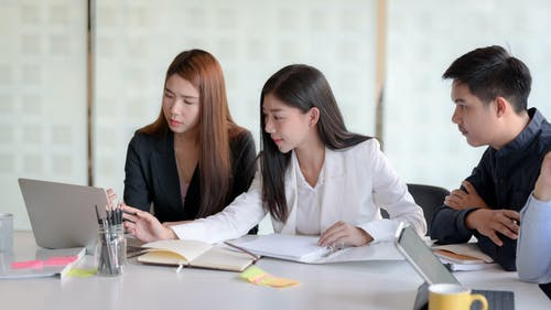 Cheerful ethnic young women working with colleagues in office