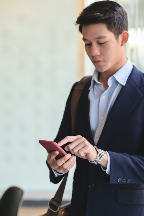 Serious young ethnic manager using smartphone in office