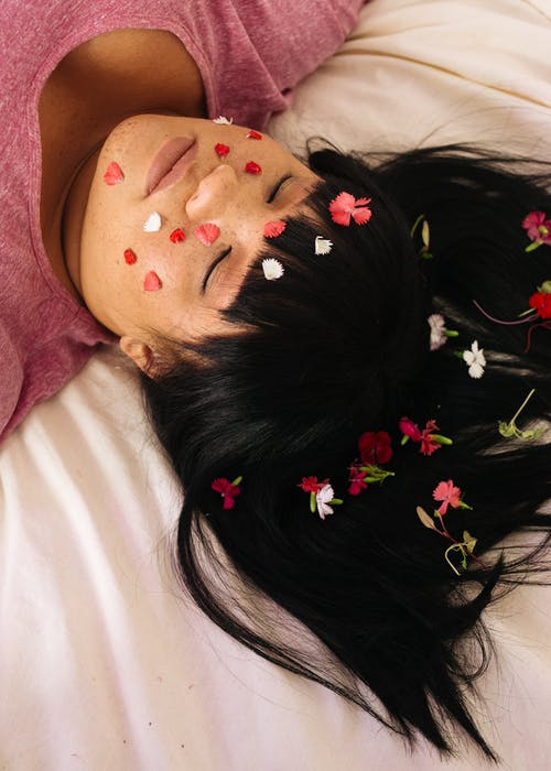 Tender plus size ethnic female with petals on face