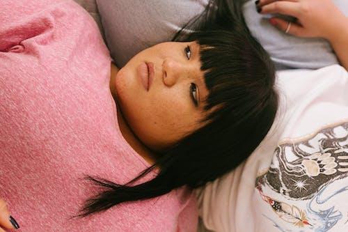 Pondering woman lying head on belly of girlfriend