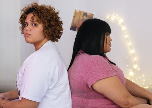 Two unhappy multiracial women in room