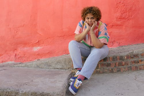Young woman in colorful clothes sitting on curb