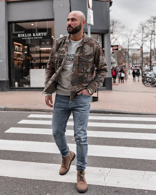 Man in Brown Leather Jacket and Blue Denim Jeans Walking on Crosswalk