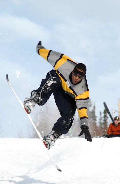 Man Riding a White Snowboard during Daytime