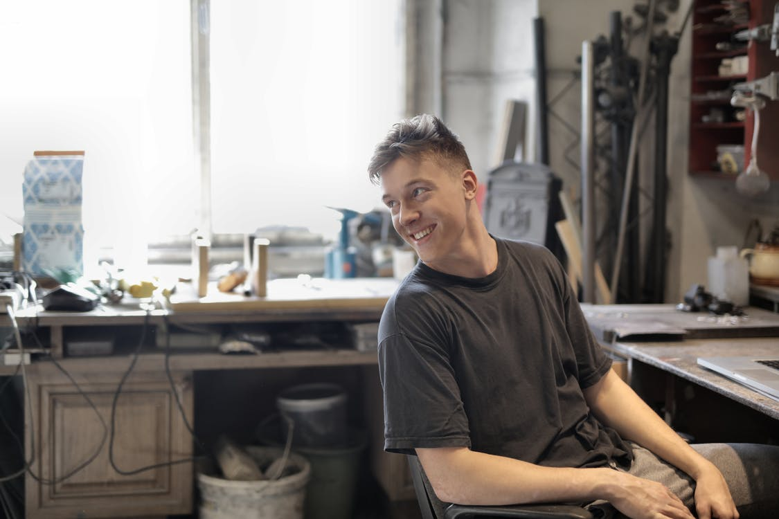 Side view of happy male in working clothes smiling and sitting at table in workshop