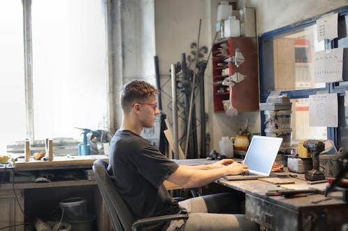 Focused man working on laptop in workshop