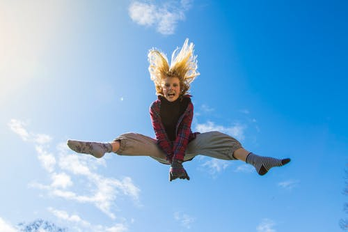 Woman Jumping Under Blue Sky