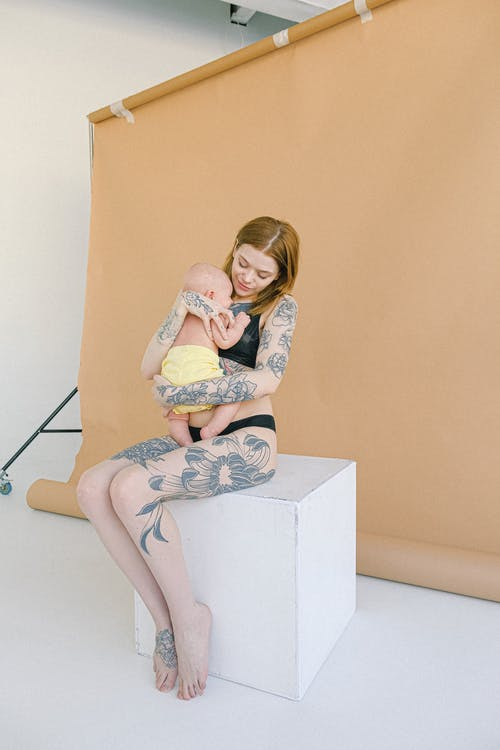 Young tattooed mother in underwear embracing newborn baby in modern studio