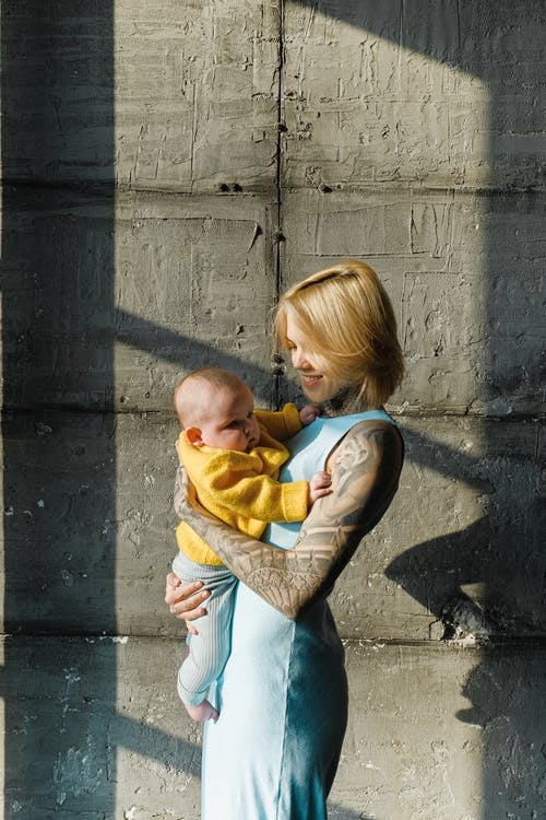 Side view of smiling tattooed woman in casual clothes embracing cute infant child while standing against gray concrete blocks in daytime