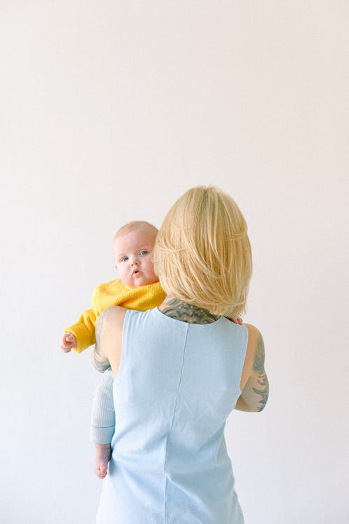 Tattooed mother hugging little baby isolated on gray background in studio