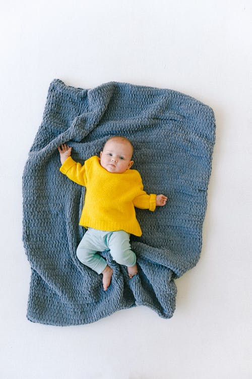 Adorable newborn baby resting on soft blue plaid in studio