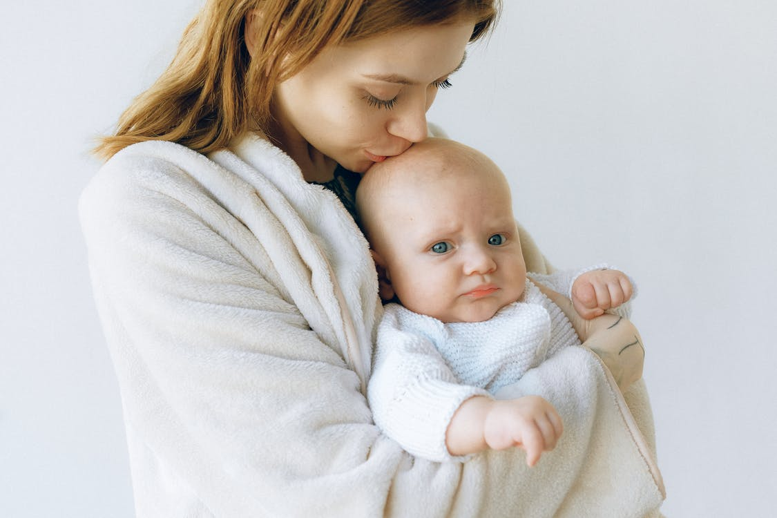 Loving mother hugging and kissing infant in photo studio