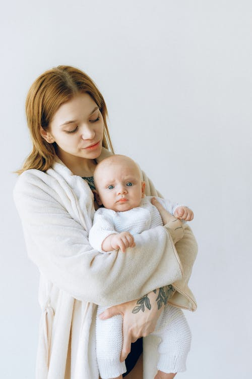 Woman in White Sweater Carrying Baby in White Onesie