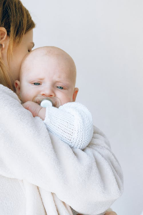 Crop mom calming sleepy baby with pacifier in mouth in light studio
