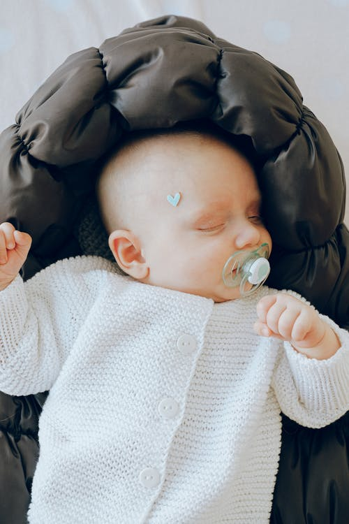 Top view of cute newborn baby in warm clothes sleeping with pacifier in mouth while resting on soft cot in studio