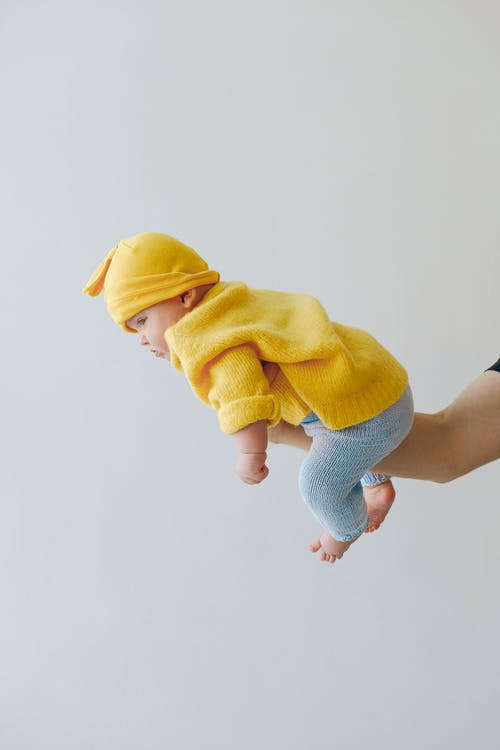 Side view full body of cute infant in warm clothes looking away while being carried by unrecognizable parent in studio