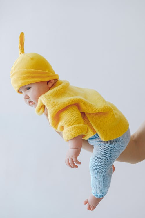 Little baby in funny hat supported by crop parent against gray background in studio