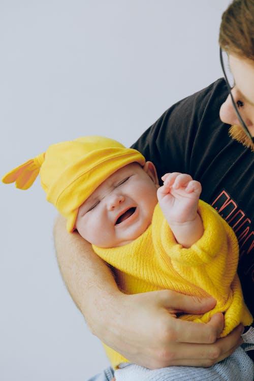 Crop father in eyewear holding moody baby in hands in studio