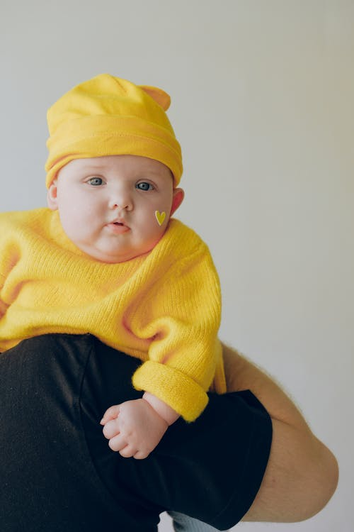 Baby in Yellow Knit Sweater and Yellow Knit Cap