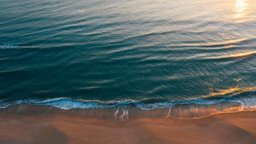 Drone picturesque view of of calm waves rolling on sandy coast and sun reflecting on turquoise water during sunset