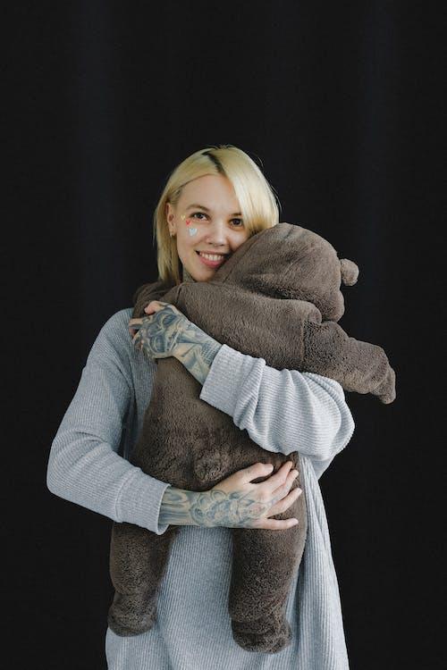 Happy mother hugging baby in bear costume in photo studio