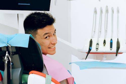 Cheerful ethnic man sitting in dental chair in modern dentist office