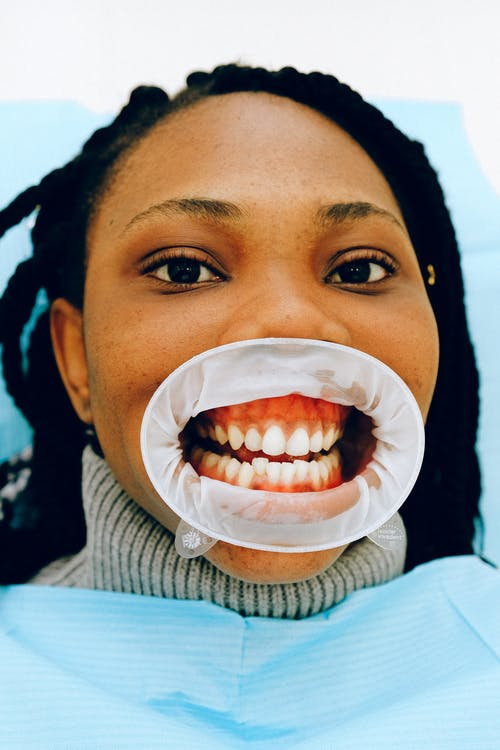 Female ethnic patient with open mouth in dental clinic