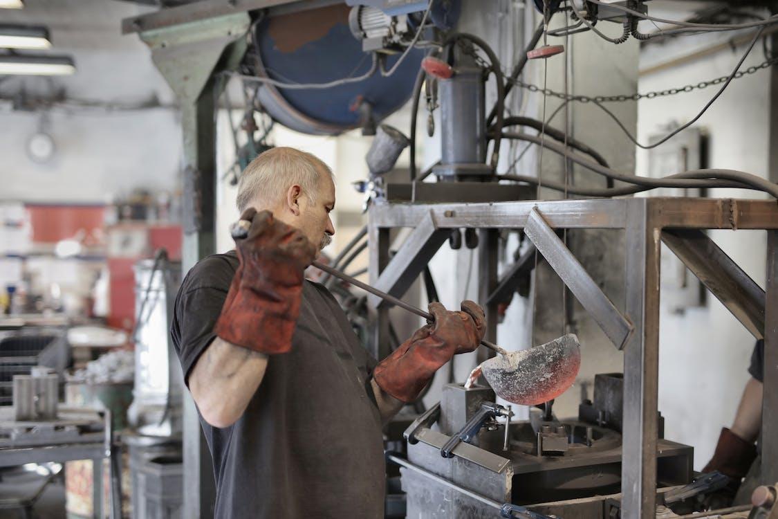 Aged white hair metallurgist working in workshop