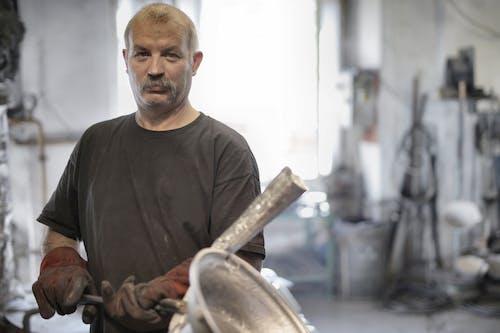 Male metallurgist working with metal in workshop