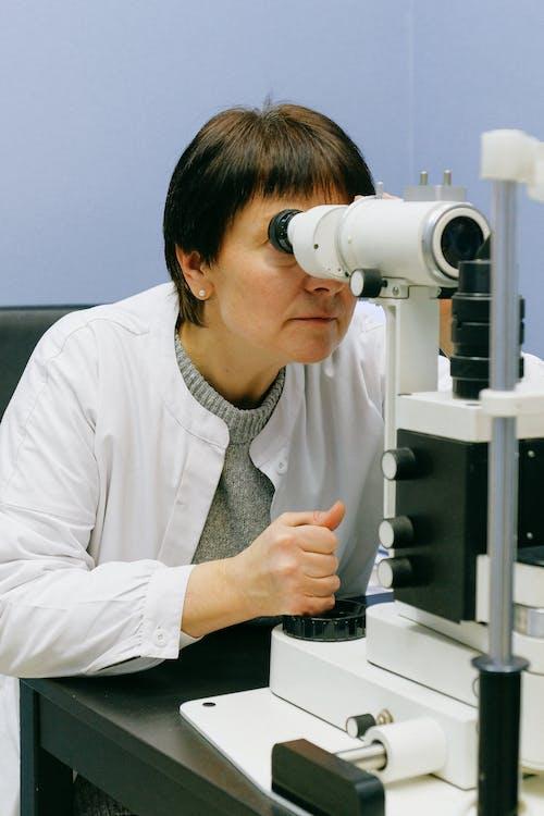 Donna In Camicia Di Vestito Bianca Facendo Uso Del Microscopio Bianco