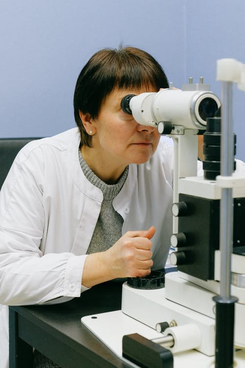 Woman in White Dress Shirt Using White Microscope